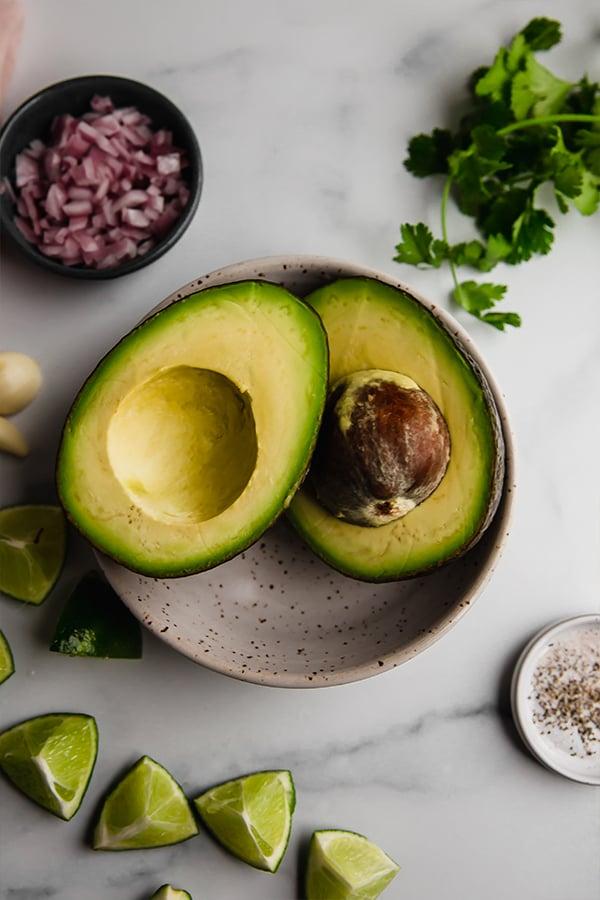 Avocado cut in half in bowl