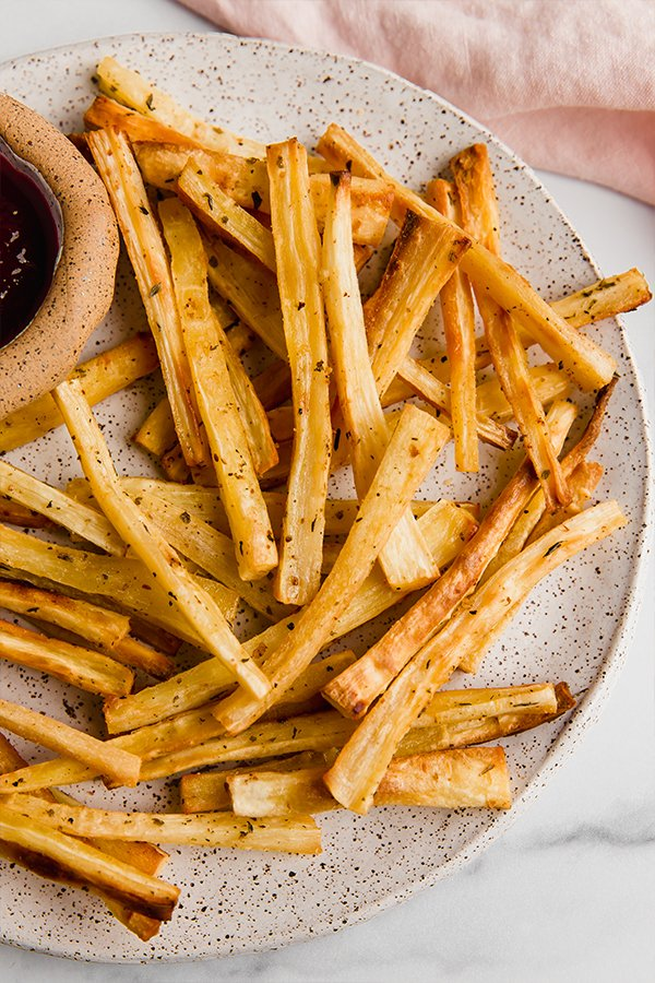 baked parsnip fries on plate with dipping sauce