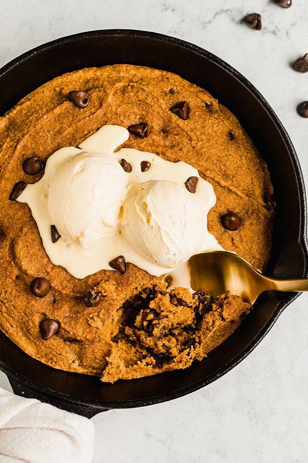 A spoon taking a bit of the pumpkin chocolate chip cookie skillet topped with ice cream.