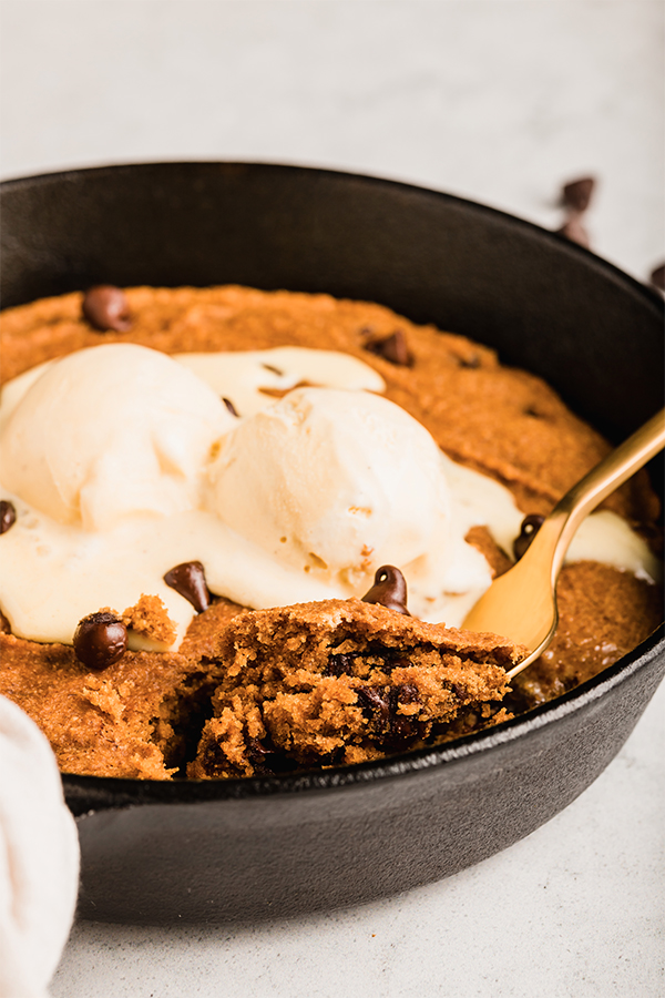 A close up of the pumpkin chocolate chip cookie skillet topped with ice cream.