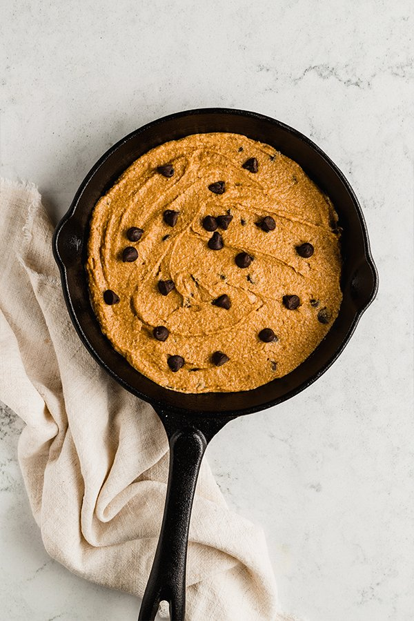 A cast iron skillet filled with pumpkin chocolate chip cookie skillet dough.