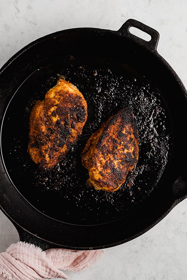 Cooked blackend chicken in cast iron skillet