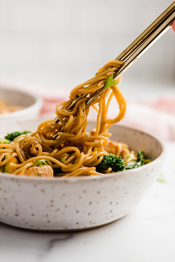 chicken and ramen stir fry in bowl with chopsticks