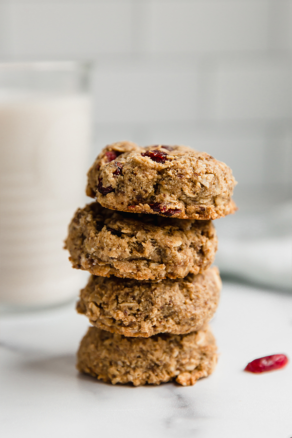 oatmeal cranberry cookies stacked on each other with glass of milk