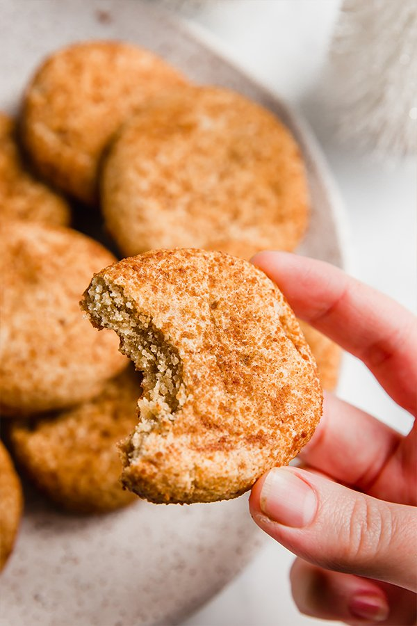snickerdoodle cookies on plate and in hand