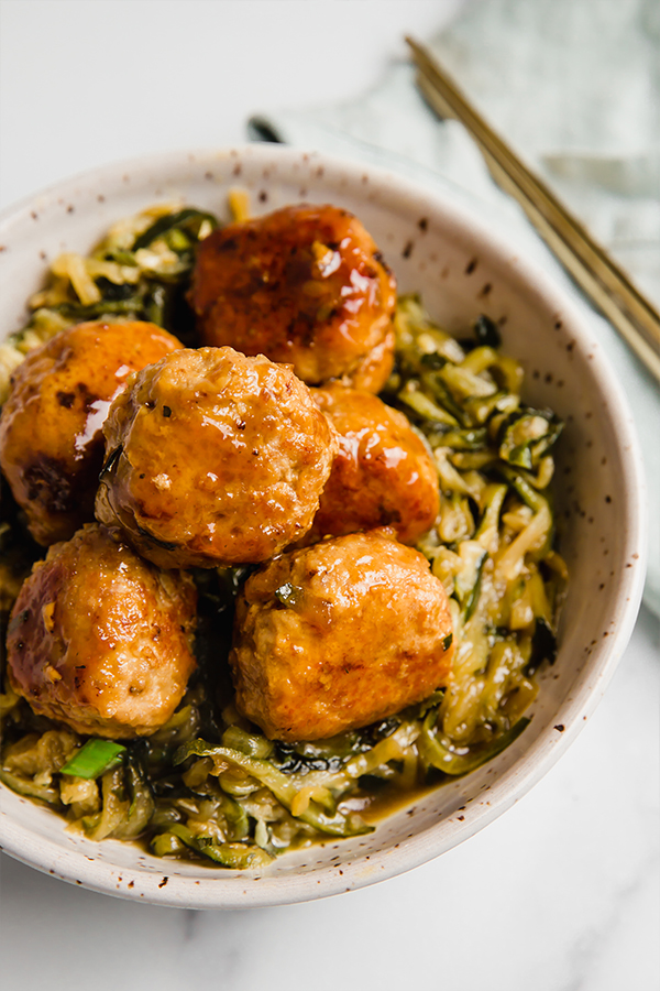 teriyaki turkey meatballs in bowl with zucchini noodles and chop sticks