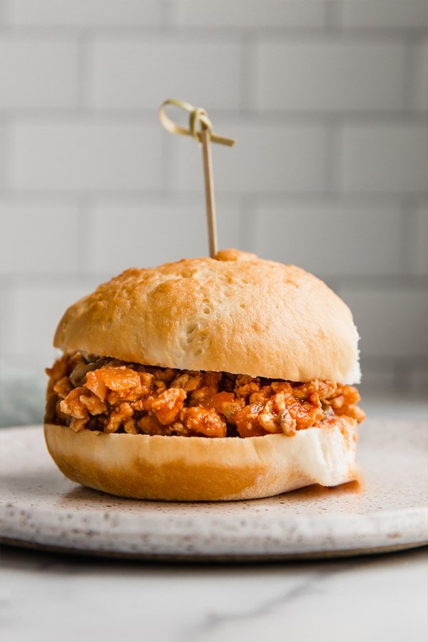turkey sloppy joe in between two bread slices with a toothpick in the middle