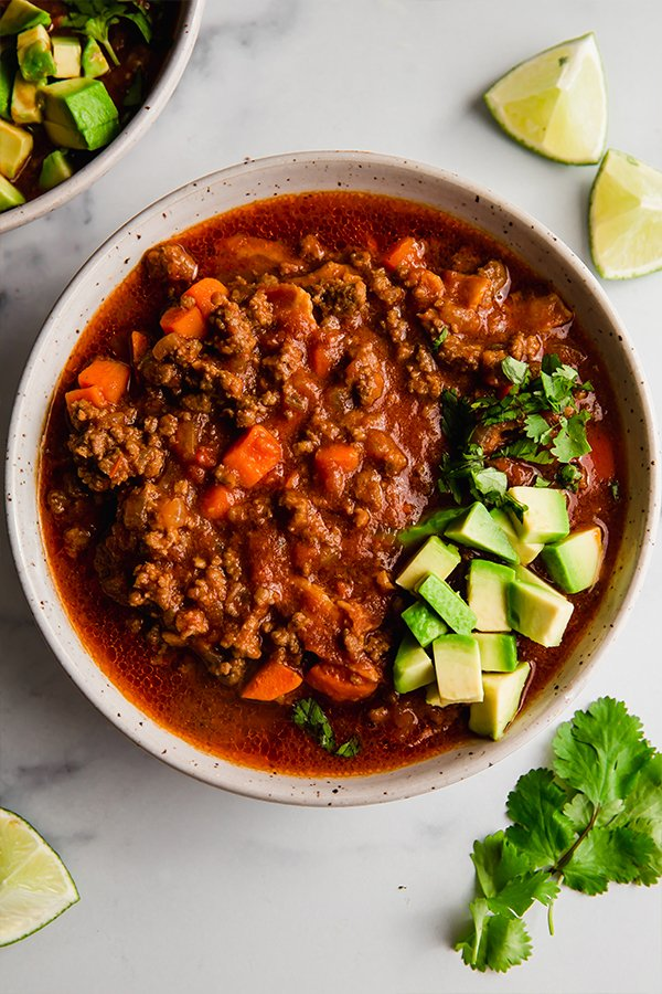 chili in a bowl with avocado and lime