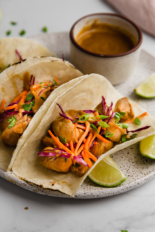 thai chicken tacos on plate with sauce