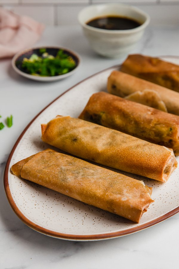 air fryer egg rolls on plate with dipping sauce on side