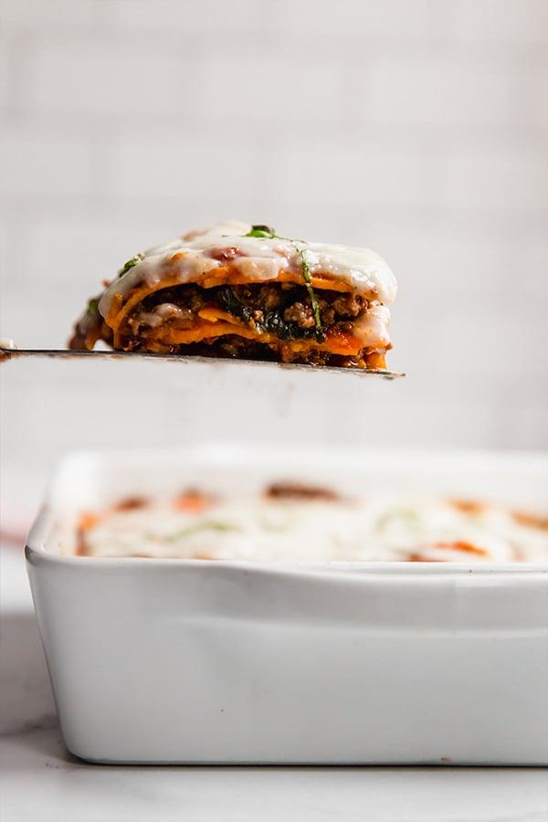 sweet potato lasagna in casserole dish with one slice on spatula