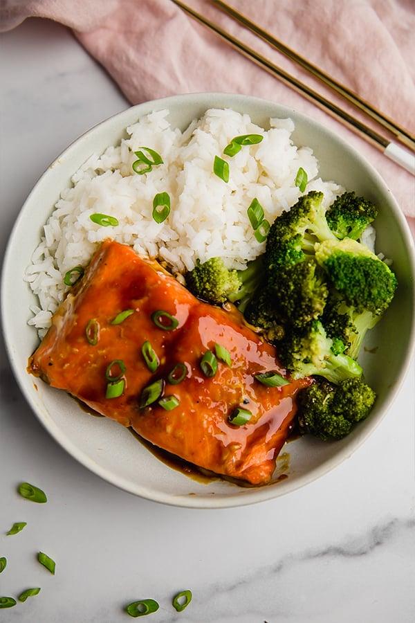 teriyaki salmon bowl with broccoli and rice, chopsticks on the side