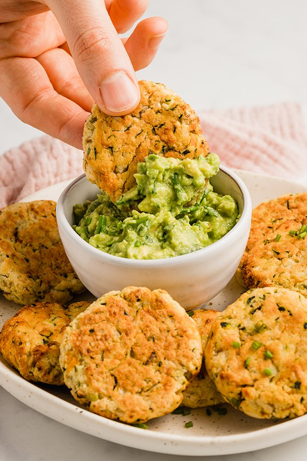 baked veggie nuggets on plate with one dipped in guacamole