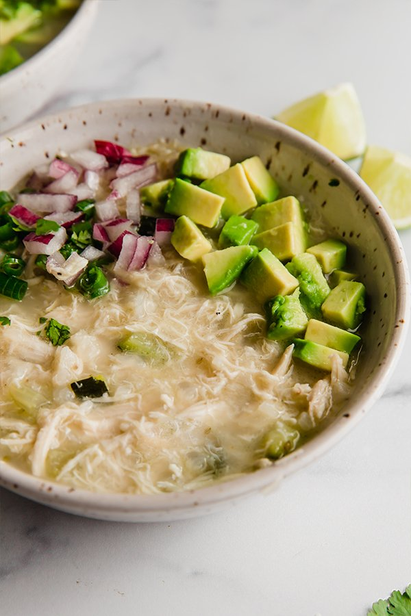 white chicken chili in bowl with avocado, red onion and lime