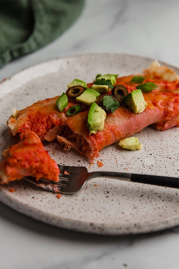 chicken enchilada on plate with fork