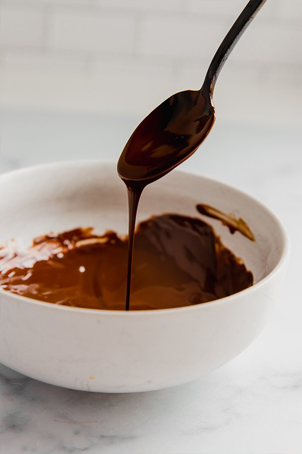 Melted chocolate in bowl with spoon