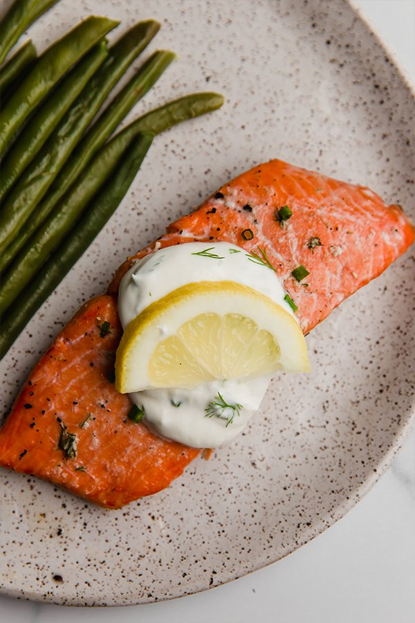 baked salmon with creamy lemon dill sauce on plate with green beans and lemon wedge