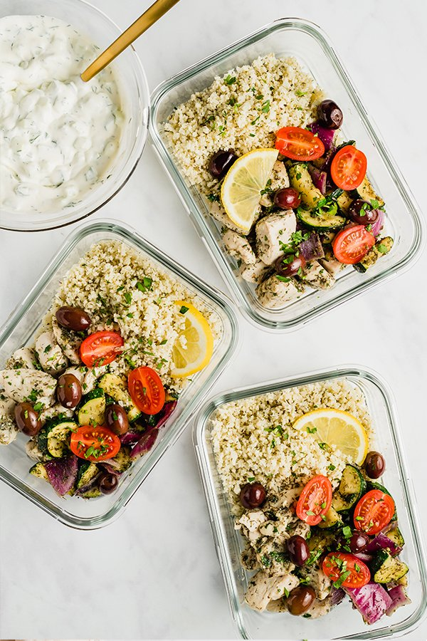 greek chicken meal prep in meal prep bowls with tzatziki sauce