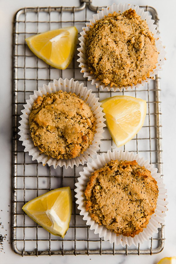 Three lemon zucchini muffins with lemon wedges