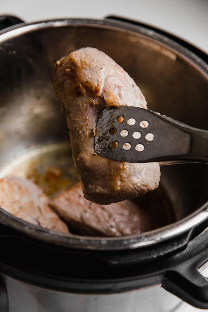 instant pot pork tenderloin slice in tongs