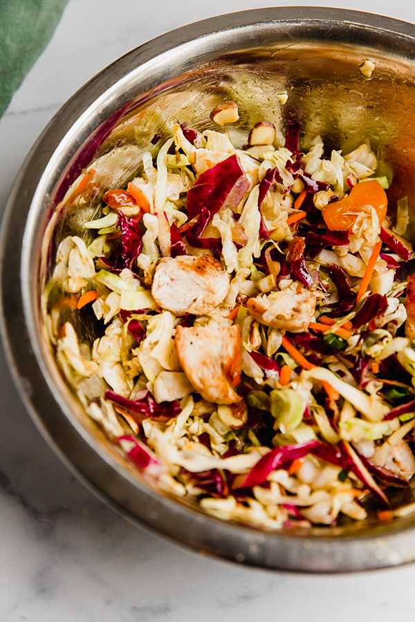 chinese chicken salad tossed in metal bowl with dressing