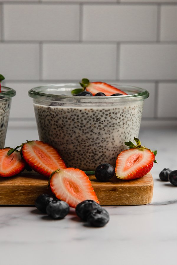 Side view of chia pudding in a jar with berries on top and displayed around