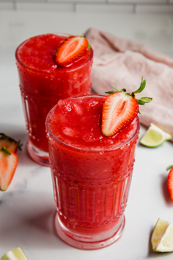 2 glasses of strawberry margaritas on counter