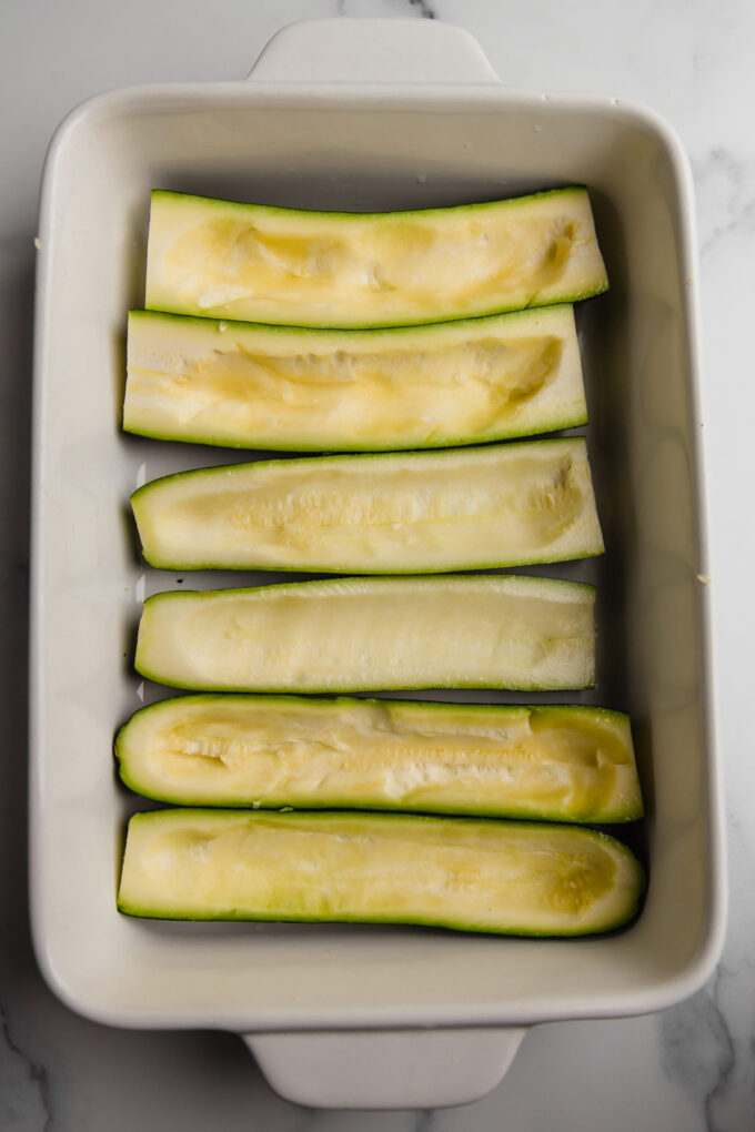 Scooped out zucchini prepared in baking dish ready for stuffing