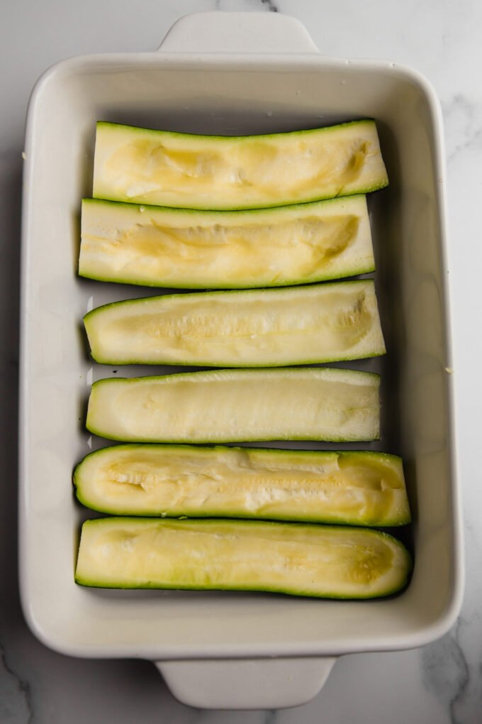 Zucchini prepped for stuffing in a baking dish