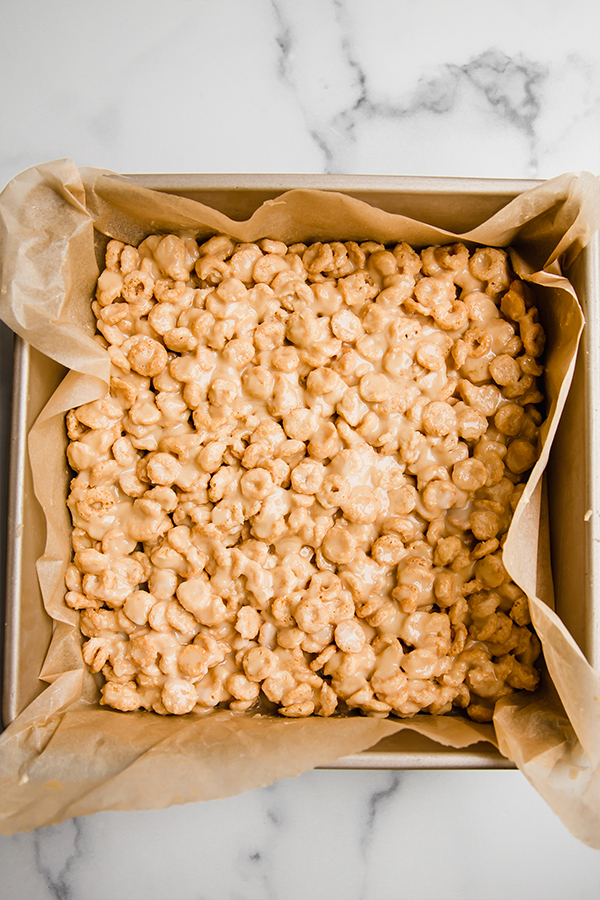 cereal bars pressd into a square pan ready to set in the fridge