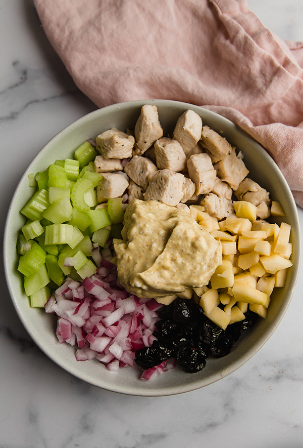Ingredients for chicken salad in bowl with curry dressing ready to mix