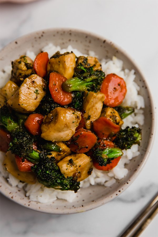 Top view of chicken stir fry in bowl over rice
