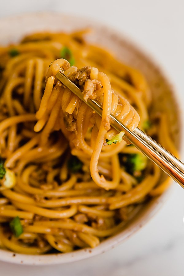 Mongolian ground beef with noodles served in a bowl with chopsticks