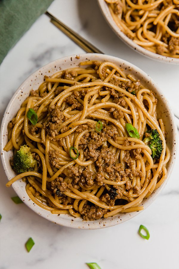 Top view of Mongolian ground beef with noodles served in a bowl with chopsticks