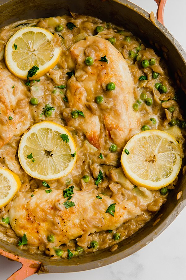Lemon chicken with orzo cooked in pan with lemon slices on top