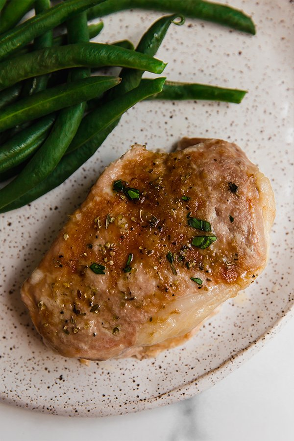 Baked pork chop on a plate with green beans