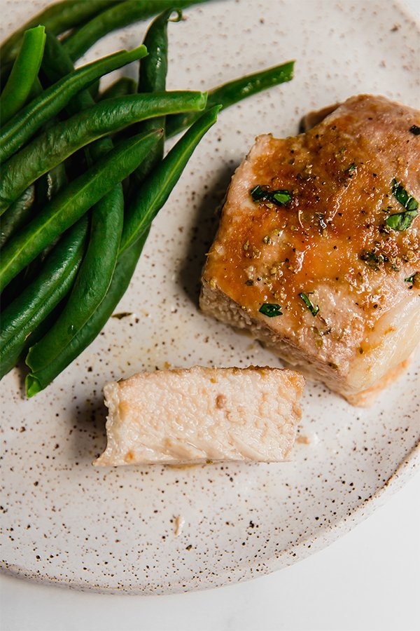 Pork chop cooked and cut with green beans on a plate