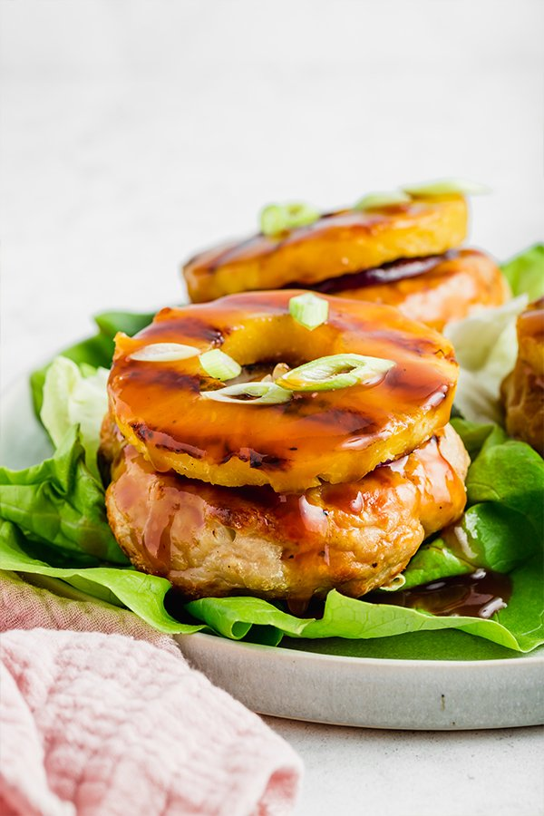 Up close side view of grilled chicken burger with pineapple ring on top