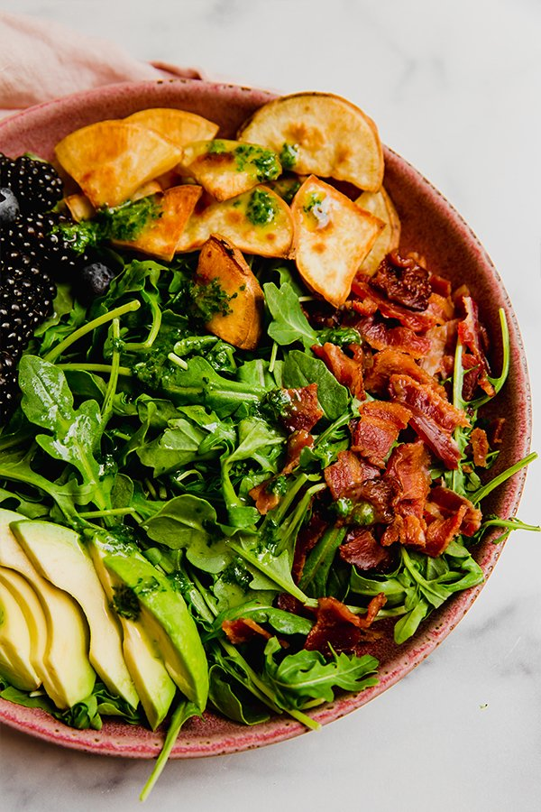 Breakfast salad topped with bacon, avocado, sweet potato, and berries