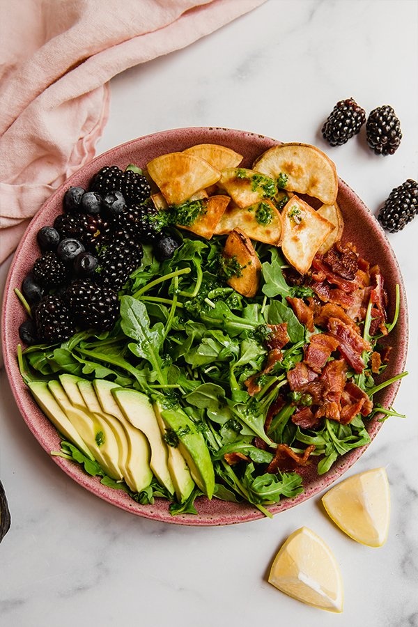 Top view of breakfast salad topped with bacon, avocado, sweet potato, and berries
