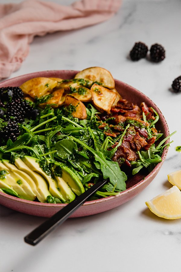 Breakfast salad topped with bacon, avocado, sweet potato, and berries served in a bowl with fork