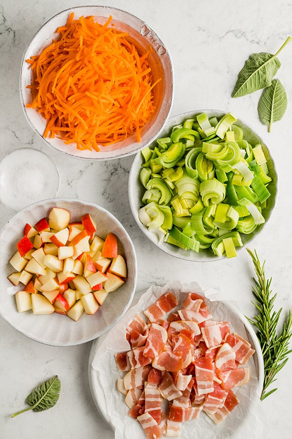 Shredded carrot, chopped leeks, chopped apples, and chopped bacon in bowls