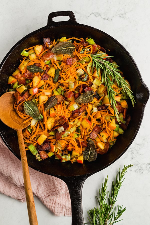 Breakfast hash cooked in cast iron skillet with wooden spoon