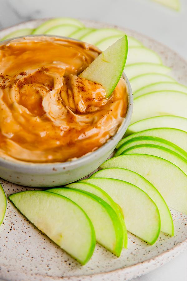 An apple slice dipping into creamy caramel apple dip.