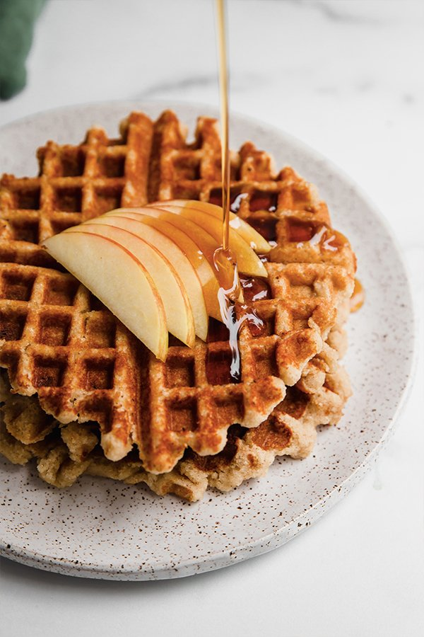 Maple syrup drizzling on a stack of gluten-free apple waffles.