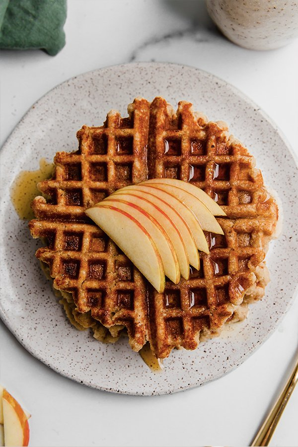 A stack of gluten-free apple waffles with sliced apples and syrup on a plate.