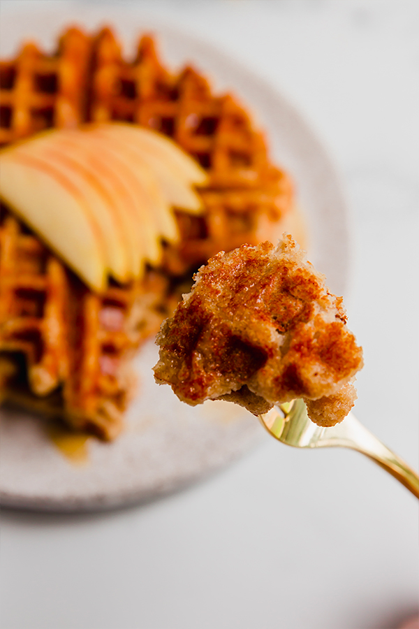 A bite of gluten-free apple waffle on a fork.