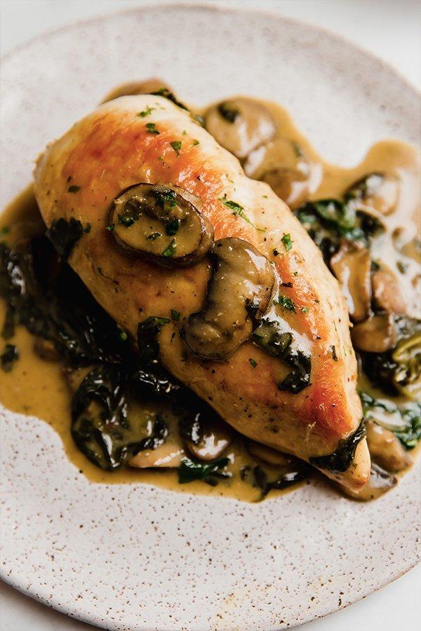 Chicken breasts with spinach and mushroom sauce served on a plate
