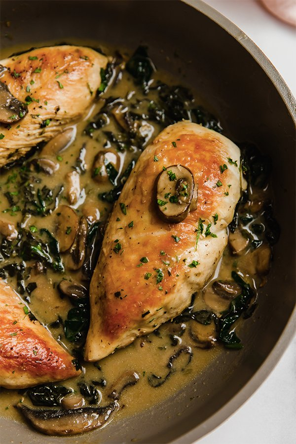 Chicken breasts cooked in pan with spinach and mushroom sauce
