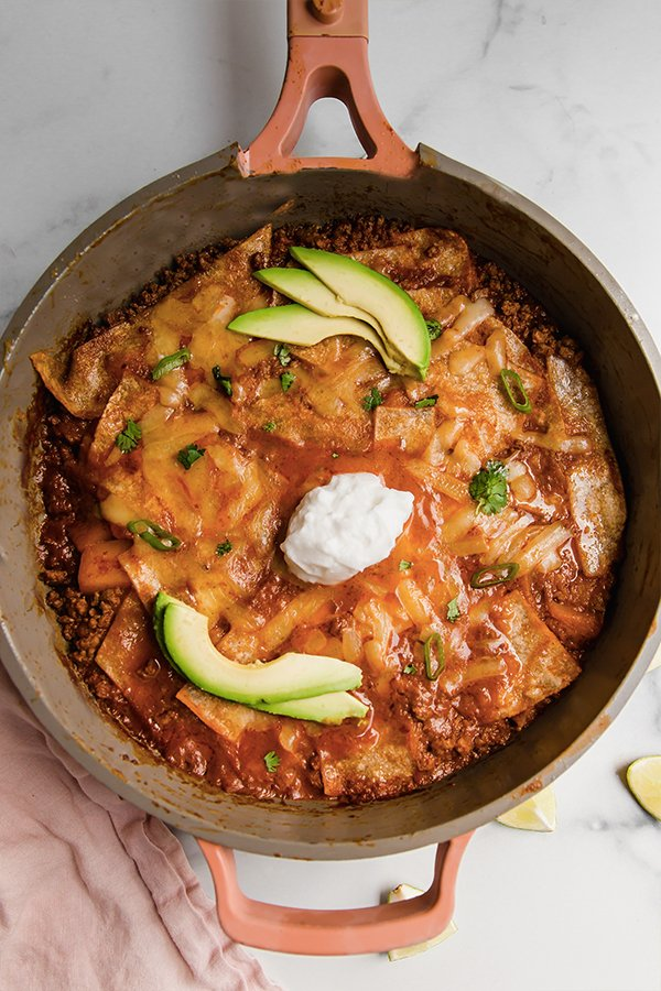 Enchilada skillet with toppings in pan ready to eat